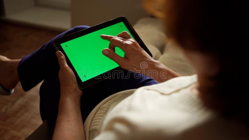Oude vrouw die een digitale tabletpc met het groene scherm, achtermening met behulp van stock fotografie