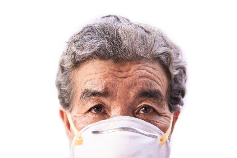 Oude vrouw die een het probleemluchtvervuiling van de maskervrees op een wit dragen stock foto