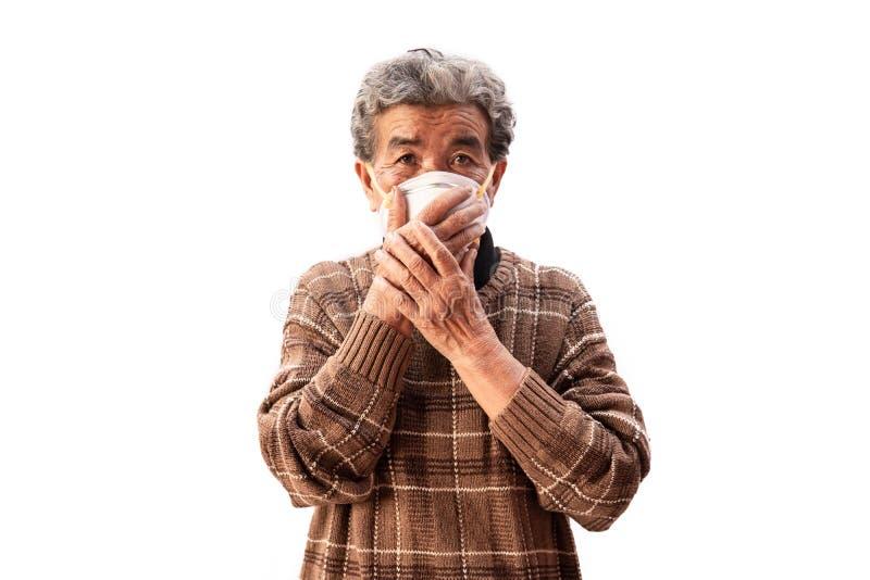 Oude vrouw die een het probleemluchtvervuiling van de maskervrees op een wit dragen stock afbeelding