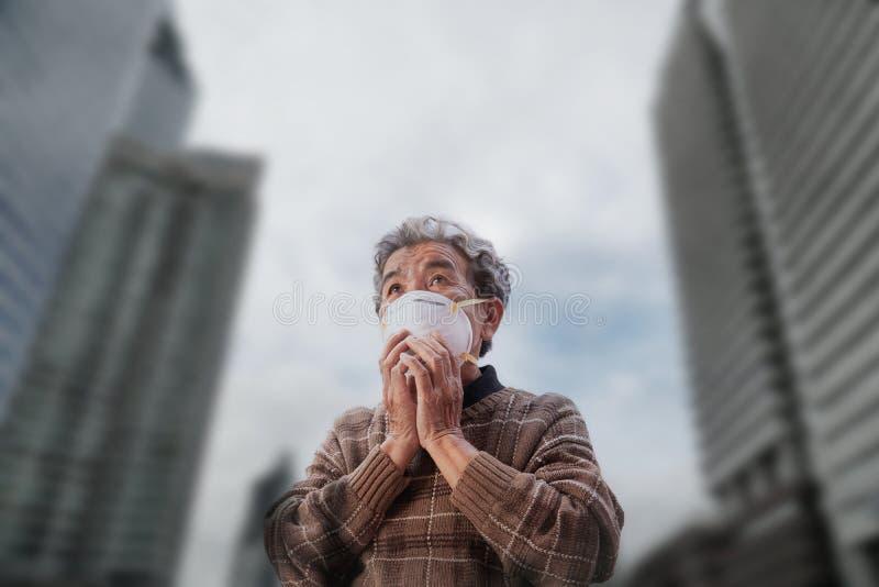 Oude vrouw die een het probleemluchtvervuiling van de maskervrees in de stad dragen stock fotografie