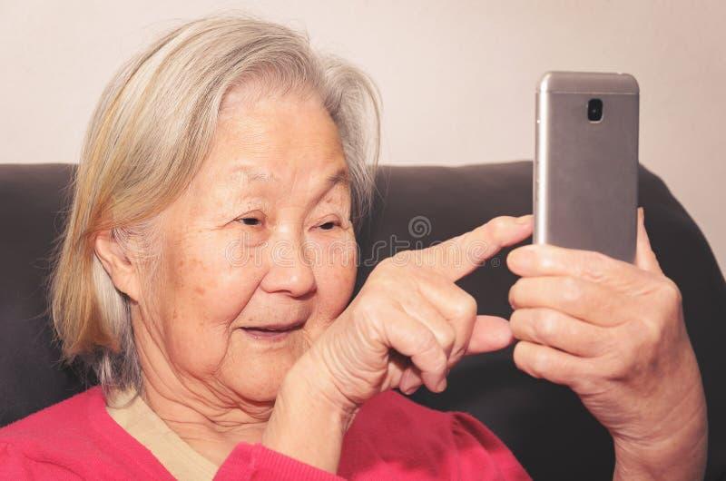 Oude vrouw die een smartphone en wat betreft het scherm houden royalty-vrije stock foto's