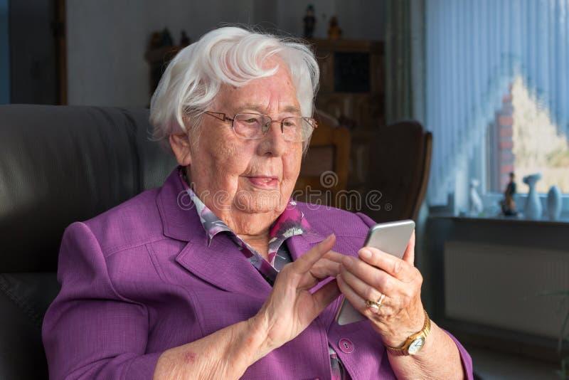 Oude vrouw die een smartphone gebruiken stock foto