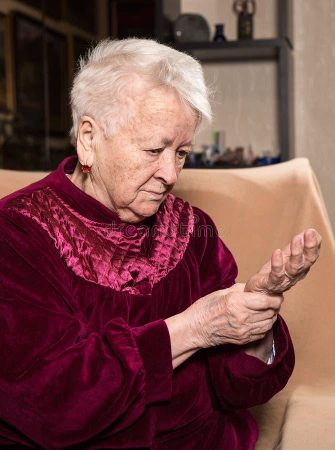 Oude vrouw die haar impuls meten stock afbeeldingen