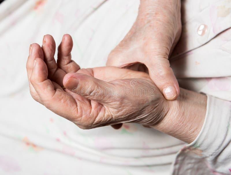 Oude vrouw die haar impuls meten stock foto