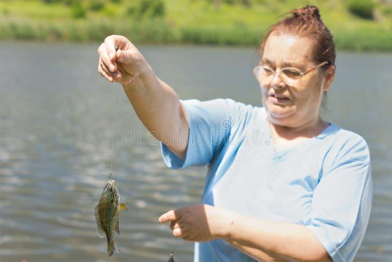Oude vrouw die haar vangst houden royalty-vrije stock foto