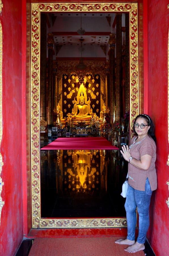 Oude vrouw die met standbeeld van Bezinnings het Gouden Boedha bidden stock afbeeldingen