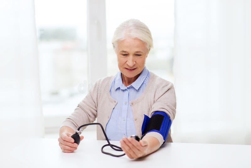 Oude vrouw die met tonometer bloeddruk controleren royalty-vrije stock foto's