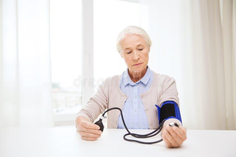 Oude vrouw die met tonometer bloeddruk controleren stock afbeelding