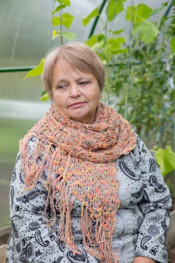 Oude vrouw die sjaal in openlucht dragen stock foto's
