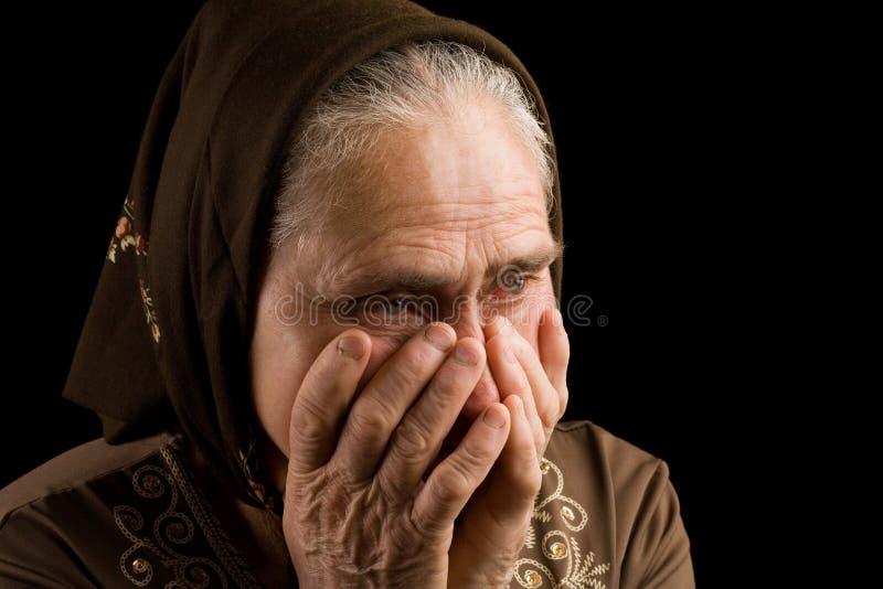 Oude vrouw in droefheid stock foto