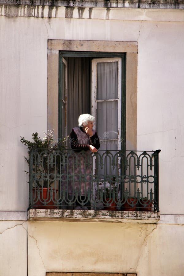 Oude vrouw in een balkon van een voorgevel van het typische huis van Lissabon stock afbeeldingen