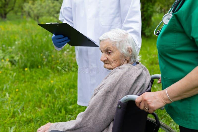 Oude vrouw in een rolstoel met medische hulp stock afbeeldingen
