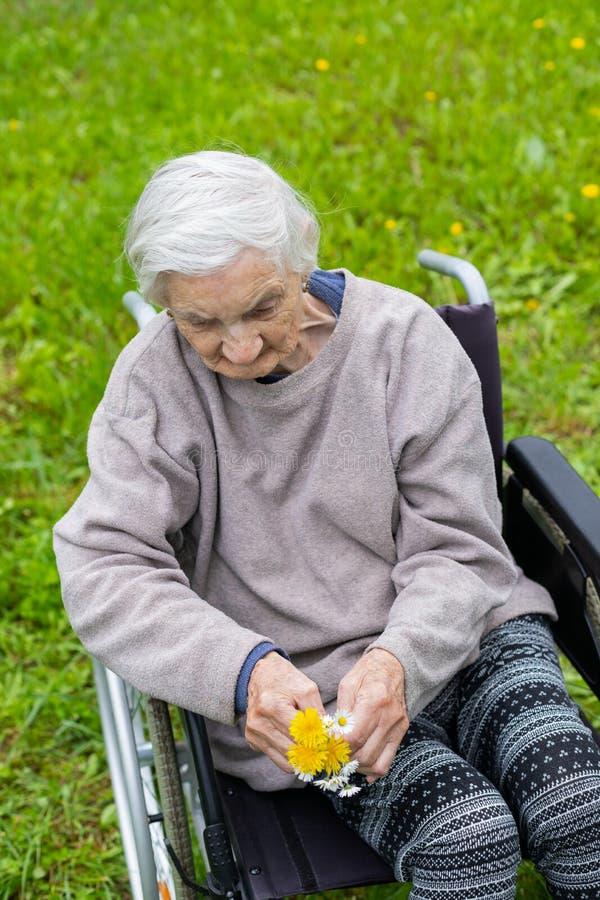 Oude vrouw in een rolstoel met medische hulp royalty-vrije stock fotografie