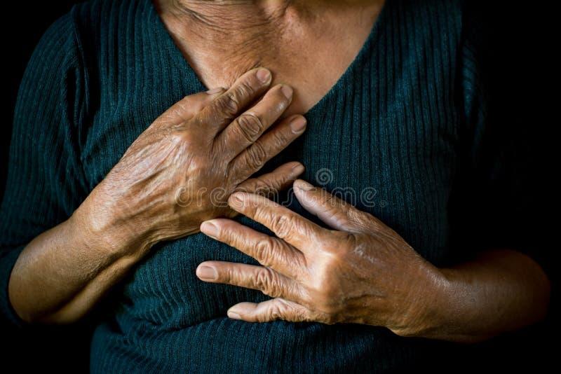 Oude vrouw gevoelde hartpijn op zwarte achtergrond royalty-vrije stock fotografie