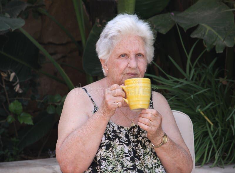 Oude vrouw het drinken thee stock foto's