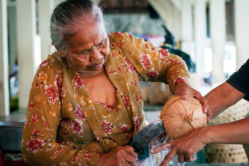 Oude vrouw het openen kokosnoot royalty-vrije stock afbeelding