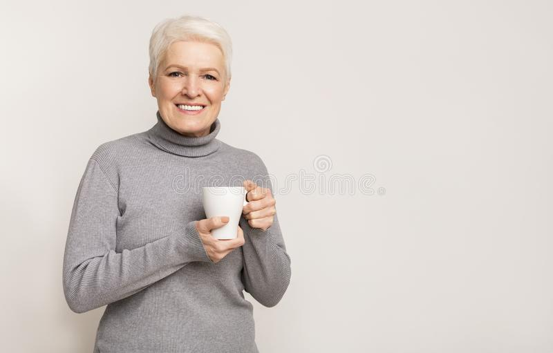 Oude vrouw houdt kopje vol met warm drinken terwijl ze opwarmt stock afbeeldingen