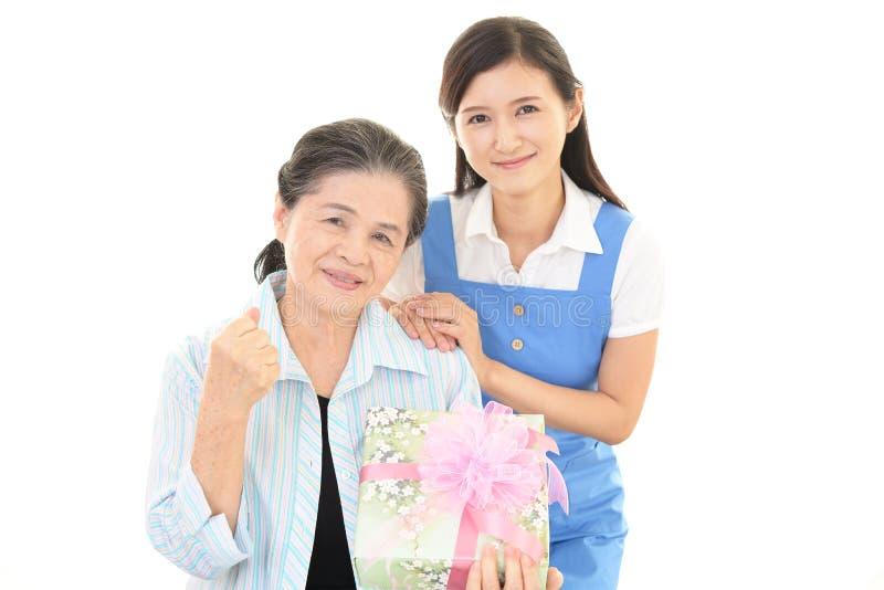 Oude vrouw met een gift stock afbeeldingen