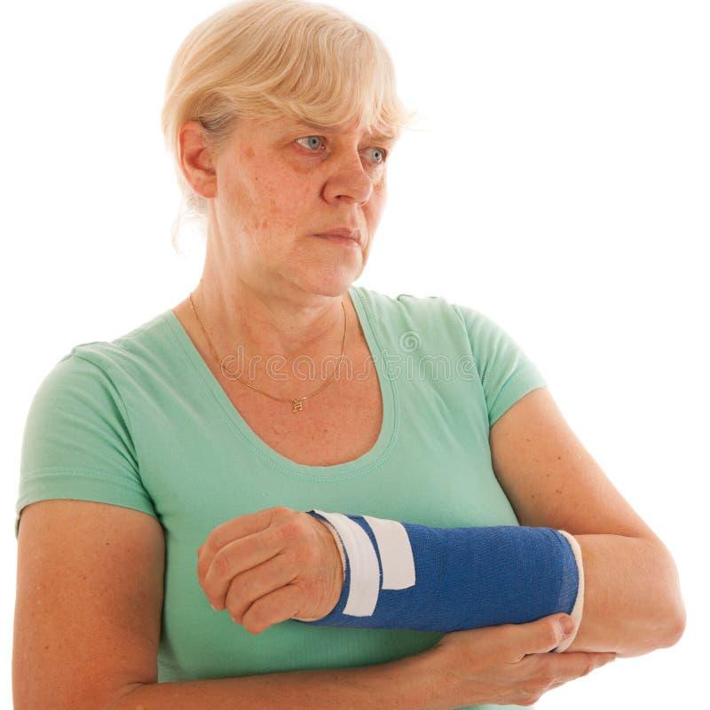 Oude vrouw met gebroken pols in gips stock foto