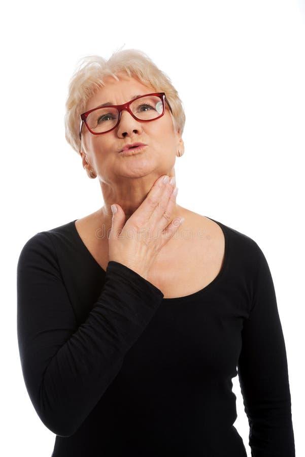 Oude vrouw met keelpijn stock foto