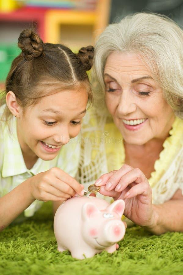 Oude vrouw met spaarvarken royalty-vrije stock foto