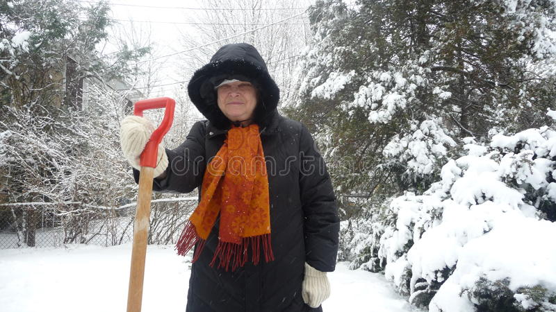 Oude vrouw met spade in sneeuw royalty-vrije stock afbeeldingen
