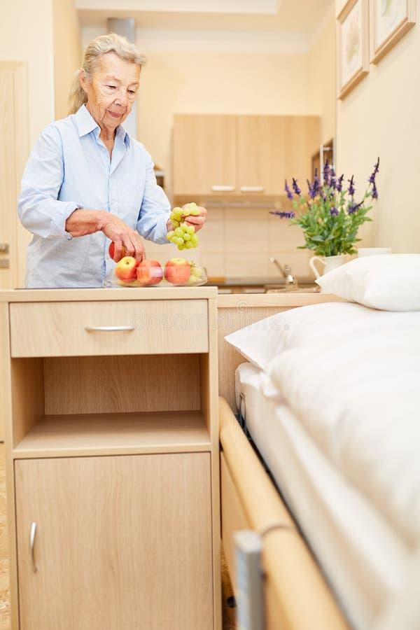 Oude vrouw met vruchten in haar bejaardeflat stock afbeelding