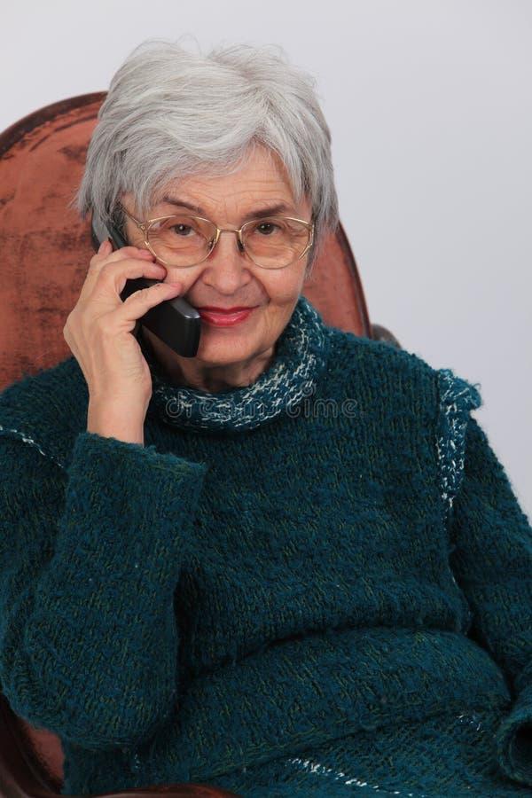 Oude vrouw op de telefoon stock fotografie