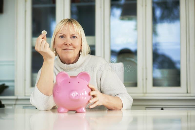 Oude vrouw piggybank en euro muntstuk die tonen royalty-vrije stock fotografie