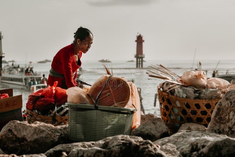 Oude Vrouw wanneer voordien het Voorbereiden van Goederen over de Badung-Straat stock fotografie
