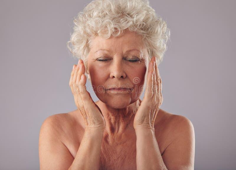 Oude vrouw wat betreft haar gezicht stock afbeelding