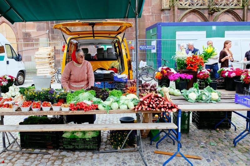 Oude vrouwelijke marktverkoper onder de Freiburg-Kathedraal, Duitsland royalty-vrije stock fotografie