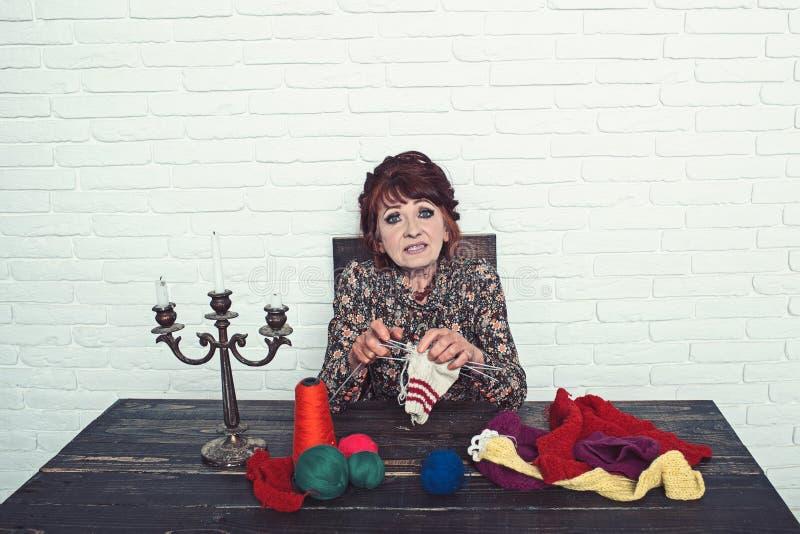 Oude vrouwen breiende sokken van kleurrijke draad stock foto's