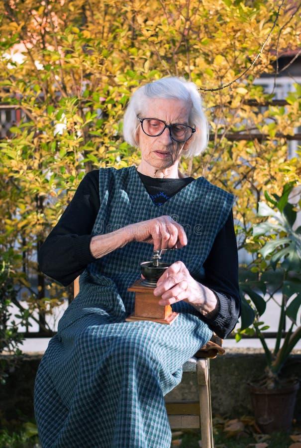 Oude vrouwen malende koffie op een uitstekende koffiemolen stock foto's