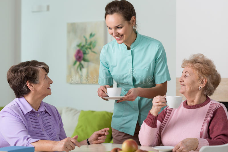 Oude vrouwen, thee en verpleegster stock foto