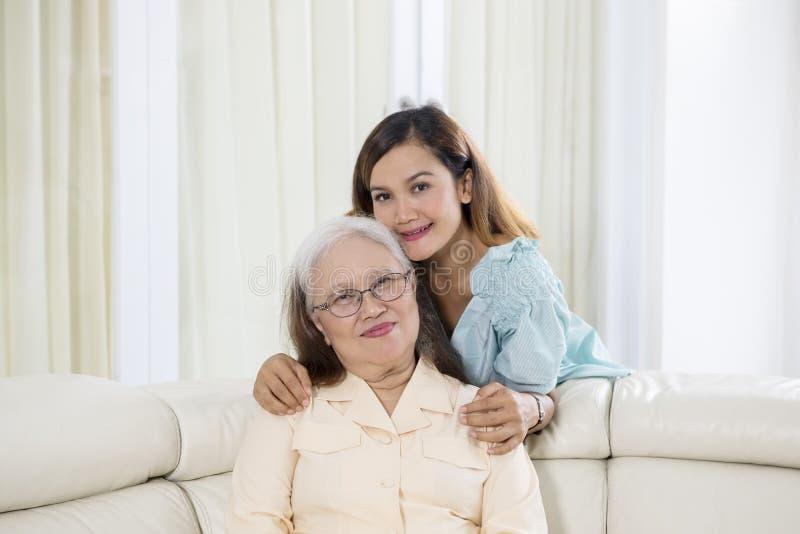 Oude vrouwenglimlachen bij de camera met haar dochter stock fotografie