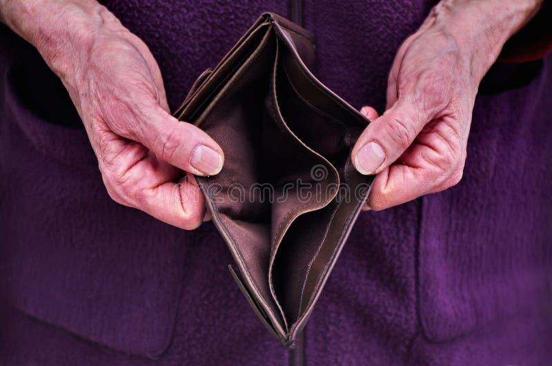 Oude vrouwenhanden die een lege portefeuille open houden Financiënproblemen royalty-vrije stock afbeelding