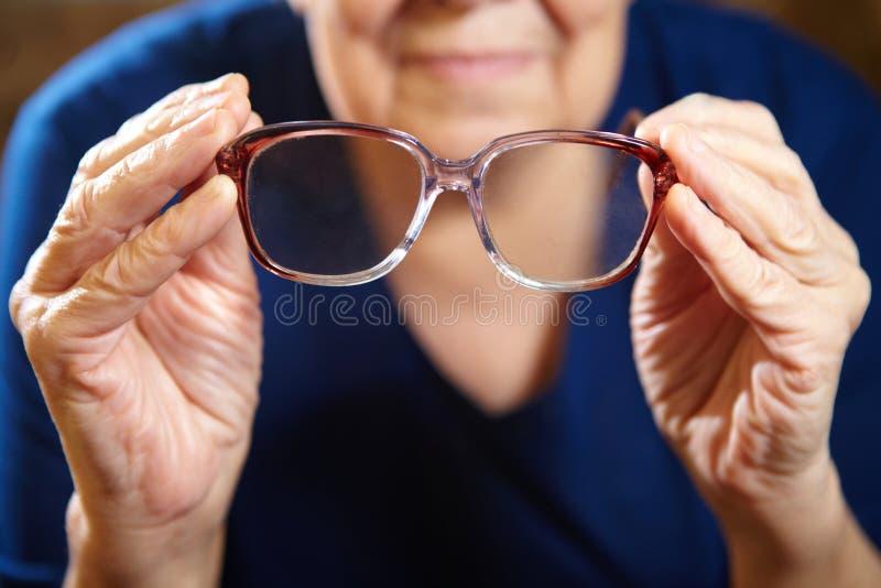 Oude vrouwenhanden met oogglazen stock foto