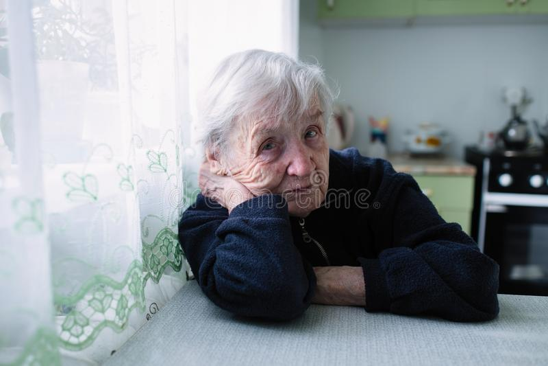 Oude vrouwenzitting in de keuken van haar flat royalty-vrije stock afbeelding