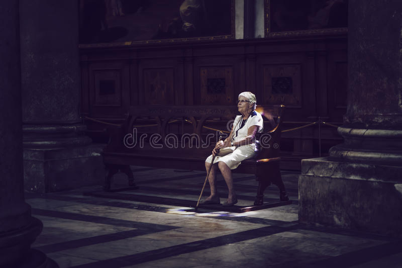 Oude vrouwenzitting in gekleurd licht op kerkbank stock afbeelding