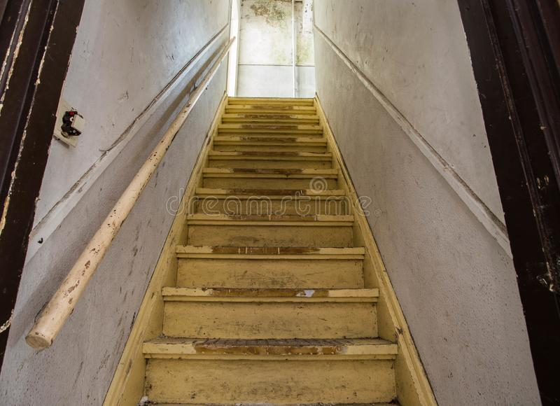 Oude vuile beschadigde verlaten houten treden aan de zolderkamer Ingang aan de zolder stock afbeelding