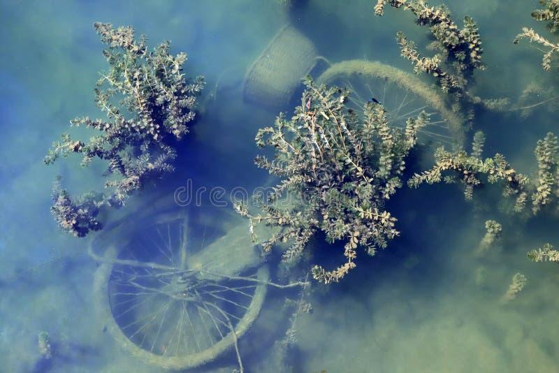 Oude vuile fiets in de diepte van het water stock afbeeldingen