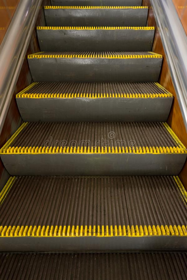 Oude vuile roltrap met gele waarschuwingsstrepen in de metro stock foto's