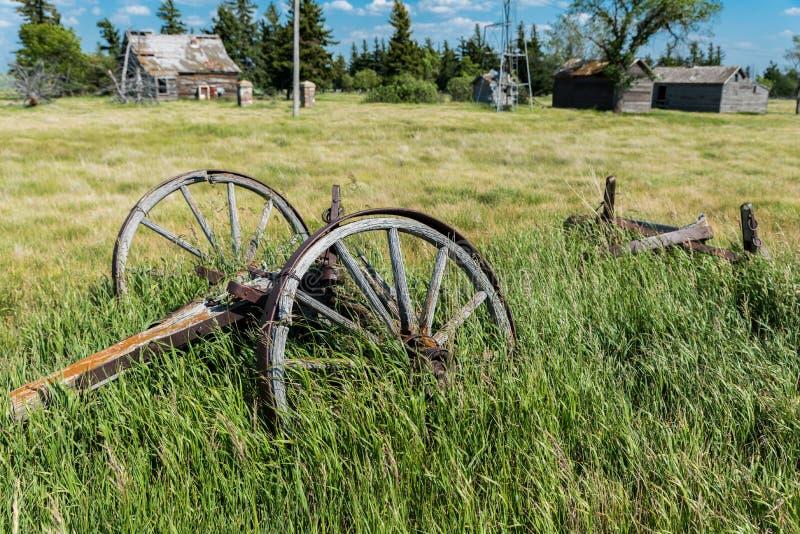 Oude wagenwielen in een verlaten prairiewerf met een oude boerderij, een windmolen, en bakken op de achtergrond royalty-vrije stock afbeeldingen