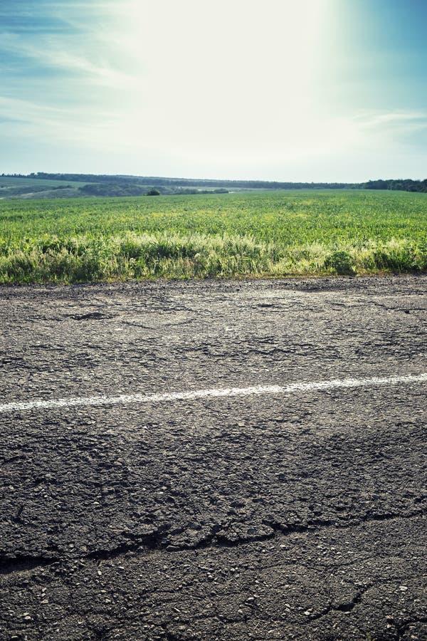 Oude weg met een het verdelen strook, een gras en een hemel op de achtergrond stock afbeeldingen