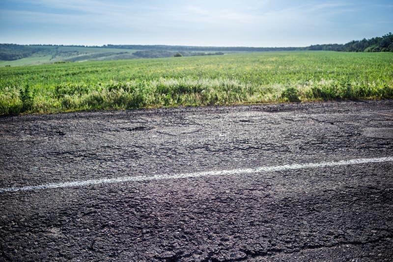 Oude weg met een het verdelen strook, een gras en een hemel op de achtergrond stock foto