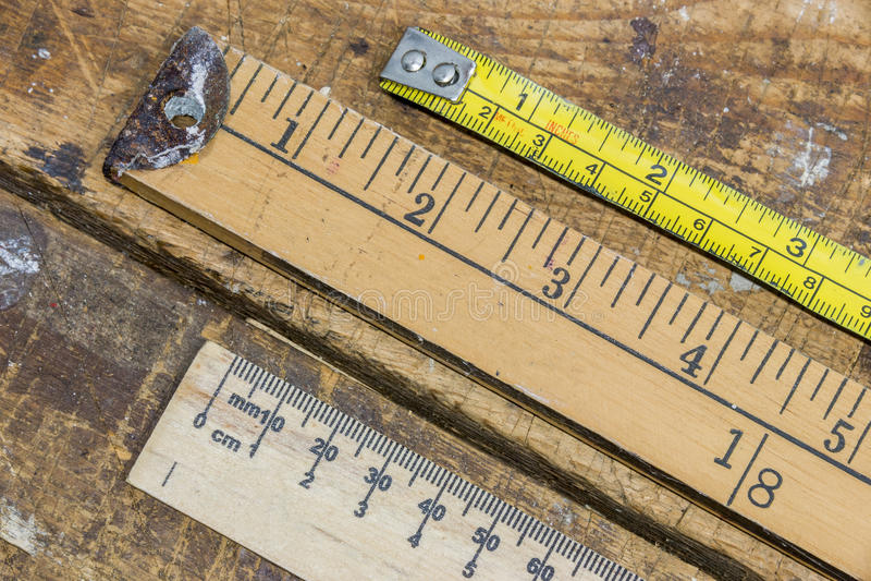Oude werfstok, heerser en meetlint op gekrast workshoplusje stock afbeelding