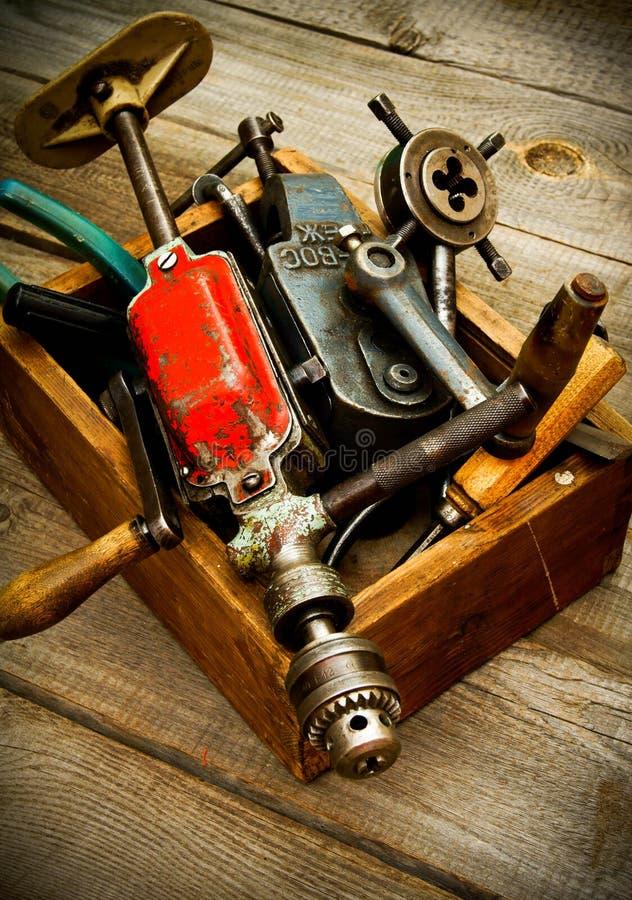 Oude werkende hulpmiddelen (boor, hamer, amaril en anderen stock foto