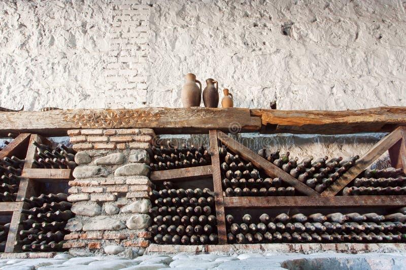 Oude wijnkelder met vele stoffige glasflessen en rustieke houten planken op steenmuren van landelijke opslag van wijnmakerij stock foto's