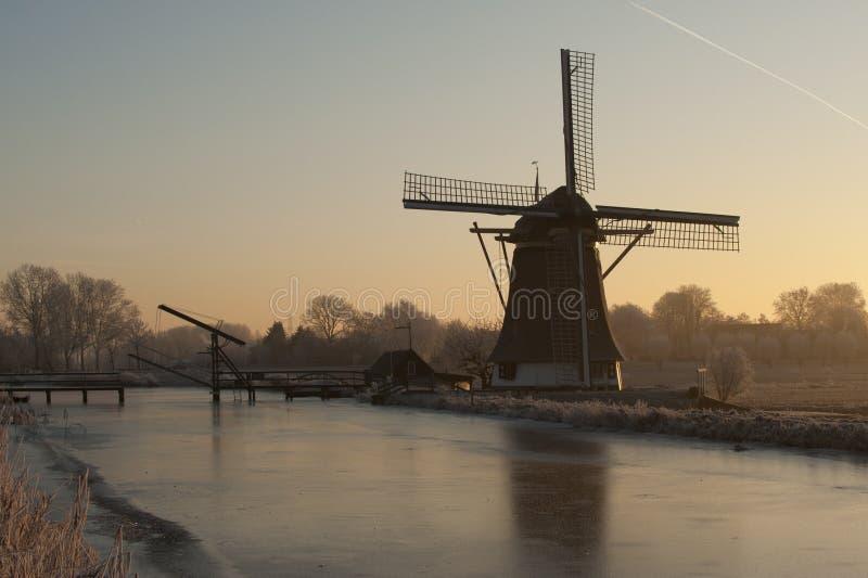 Oude Windmolen langs bevroren rivier royalty-vrije stock afbeelding